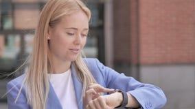 Giovane donna di affari che usando smartwatch all'aperto video d archivio