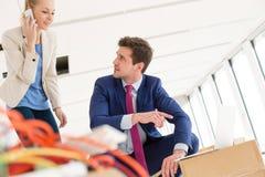 Giovane donna di affari che utilizza telefono cellulare mentre collega maschio che indica verso il computer portatile nel nuovo u Immagini Stock