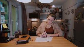 Giovane donna di affari con i documenti che si siedono alla tavola e che lavorano con le carte Lavoro straordinario a casa stock footage