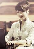 Giovane donna di affari con il computer portatile al caffè del marciapiede Fotografia Stock