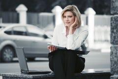 Giovane donna di affari con il computer portatile che si siede all'edificio per uffici Fotografie Stock