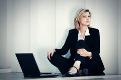 Giovane donna di affari con il computer portatile che si siede alla parete Immagine Stock