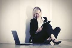 Giovane donna di affari con il computer portatile che si siede alla parete fotografia stock libera da diritti