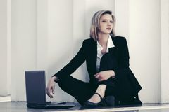 Giovane donna di affari con il computer portatile che si siede alla parete immagini stock