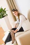 Giovane donna di affari con il sacchetto di acquisto sul sofà Fotografie Stock