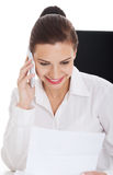 Giovane donna di affari con il telefono, sedentesi dallo scrittorio. fotografie stock libere da diritti