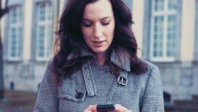 Giovane donna di affari con lo smartphone fuori dell'ufficio stock footage