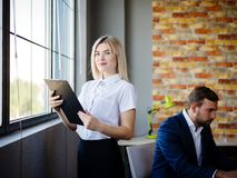 Giovane donna di affari con una cartella sui precedenti di un lavoratore Fotografia Stock