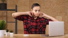 Giovane donna di affari dei pantaloni a vita bassa che sbadiglia al suo scrittorio in ufficio video d archivio