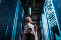 Giovane donna di affari dell'ingegnere nella stanza del server di rete Immagine Stock