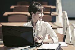 Giovane donna di affari di modo che per mezzo del computer portatile al caffè del marciapiede Fotografie Stock