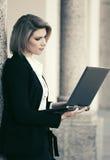 Giovane donna di affari di modo con il computer portatile all'edificio per uffici Fotografie Stock