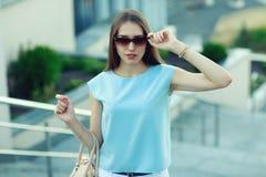 Giovane donna di affari di modo in occhiali da sole su una via della città Immagini Stock Libere da Diritti