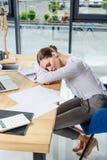 Giovane donna di affari esaurita che dorme al suo scrittorio all'ufficio davanti a immagini stock