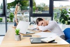 Giovane donna di affari esaurita che dorme al suo scrittorio all'ufficio davanti a fotografia stock libera da diritti