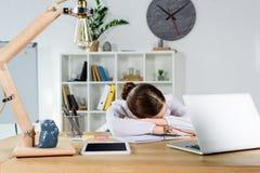 Giovane donna di affari esaurita che dorme al suo scrittorio all'ufficio davanti a fotografie stock libere da diritti