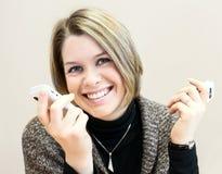 Giovane donna di affari felice attraente che chiacchiera su due smartphones Immagini Stock Libere da Diritti
