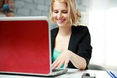 Giovane donna di affari felice che per mezzo del computer portatile Fotografia Stock