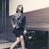 Giovane donna di affari di modo che si siede sullo strato nell'interno dell'ufficio immagine stock