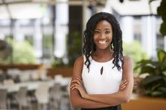 Giovane donna di affari nera sorridente con le armi attraversate immagine stock