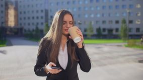 Giovane donna di affari o studentessa caucasica professionista, donna che cammina e che per mezzo del telefono cellulare, smartph video d archivio