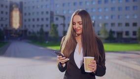 Giovane donna di affari o studentessa professionista, donna che cammina e che per mezzo del telefono cellulare, smartphone, manda video d archivio