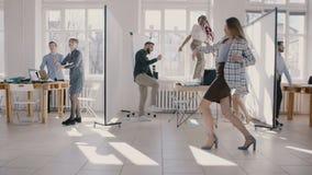 Giovane donna di affari pazza che balla insieme ai colleghi multietnici che celebrano il movimento lento di successo di carriera  stock footage