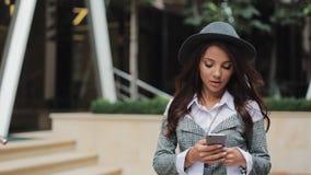 Giovane donna di affari professionale che cammina sulla via urbana facendo uso dello smartphone Concetto: nuovo affare, comunicaz video d archivio