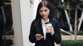 Giovane donna di affari professionale che cammina sulla via urbana facendo uso dello smartphone e del caffè della bevanda Concett archivi video