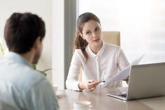Giovane donna di affari sicura che discute riassunto con schietto maschio Fotografia Stock Libera da Diritti
