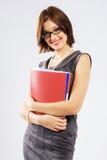 Giovane donna di affari sicura con i dispositivi di piegatura Immagini Stock Libere da Diritti