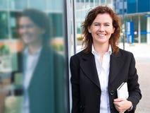 Giovane donna di affari sicura con la cartella vicino alla configurazione dell'ufficio immagine stock