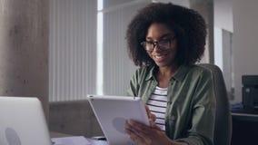 Giovane donna di affari sicura sorridente che per mezzo della compressa digitale archivi video