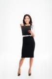 Giovane donna di affari sorridente amichevole con la lavagna per appunti che indica matita alla macchina fotografica Fotografia Stock Libera da Diritti