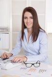 Giovane donna di affari sorridente attraente che lavora allo scrittorio all'ufficio. Immagine Stock