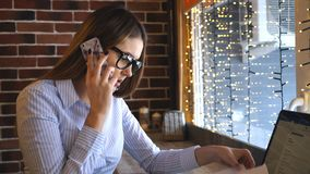 Giovane donna di affari sorridente che parla sul telefono all'impiegato di concetto felice del caffè che rende affare o chiamata  archivi video