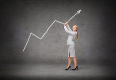 Giovane donna di affari sorridente che spinge verso l'alto freccia Immagine Stock