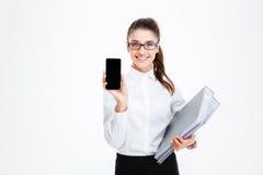 Giovane donna di affari sorridente con le cartelle che mostrano il telefono cellulare dello schermo in bianco Fotografia Stock