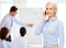 Giovane donna di affari sorridente con lo smartphone Immagini Stock