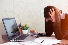 Giovane donna di affari stanca da lavoro nell'ufficio fotografie stock