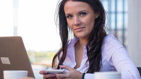 Giovane donna di affari su una pausa caffè facendo uso del telefono cellulare. Fotografia Stock Libera da Diritti