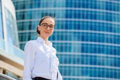 Giovane donna di affari sui precedenti dei grattacieli Fotografie Stock Libere da Diritti