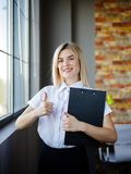 Giovane donna di affari in una blusa bianca con una cartella del primo piano Immagine Stock