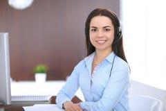 Giovane donna di affari in una cuffia avricolare, sedentesi alla tavola nell'ufficio Immagini Stock