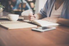 Giovane donna di affari in vestito bianco che si siede alla tavola in caffè e che scrive in taccuino Smartphone di conversazione  Fotografia Stock