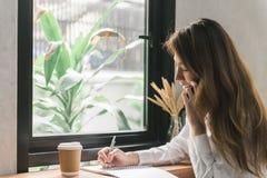 Giovane donna di affari in vestito bianco che si siede alla tavola in caffè e che scrive in taccuino Smartphone di conversazione  Fotografie Stock