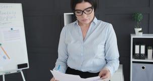 Giovane donna di affari in vetri sul lavoro archivi video