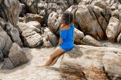 Giovane donna di Atrractive che si siede sulla pietra al giorno soleggiato caldo sopra Fotografia Stock