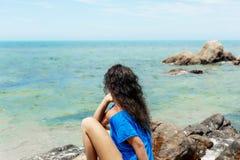 Giovane donna di Atrractive che si siede sulla pietra al giorno soleggiato caldo sopra Immagine Stock