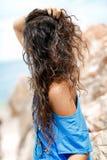 Giovane donna di Atrractive che si siede sulla pietra al giorno soleggiato caldo sopra Fotografie Stock Libere da Diritti